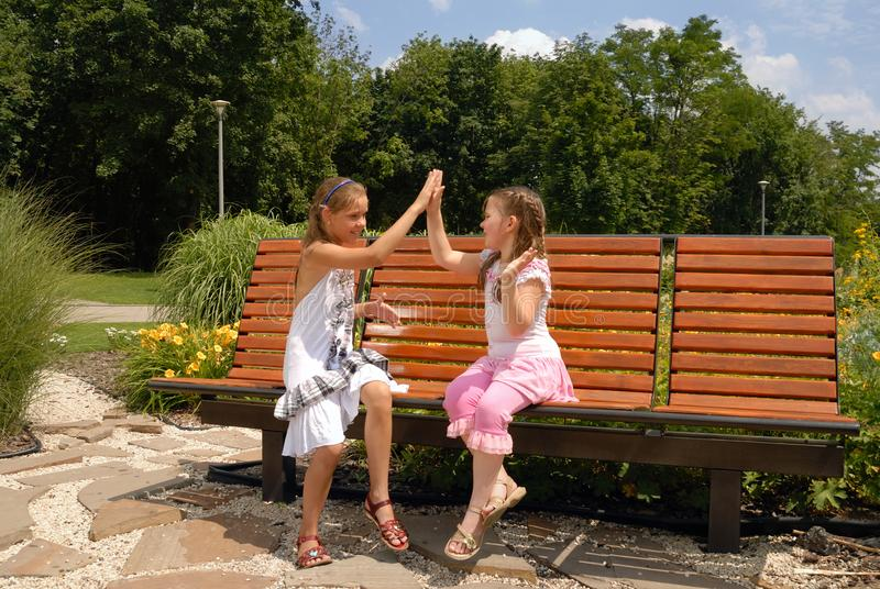Two Girls On a Bench Play Pat-a-Cake. Playing Children in Park stock image