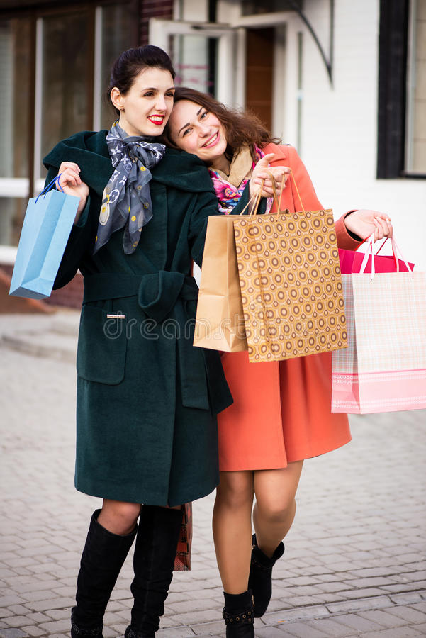 Two girls best friends returning from shopping stock photography