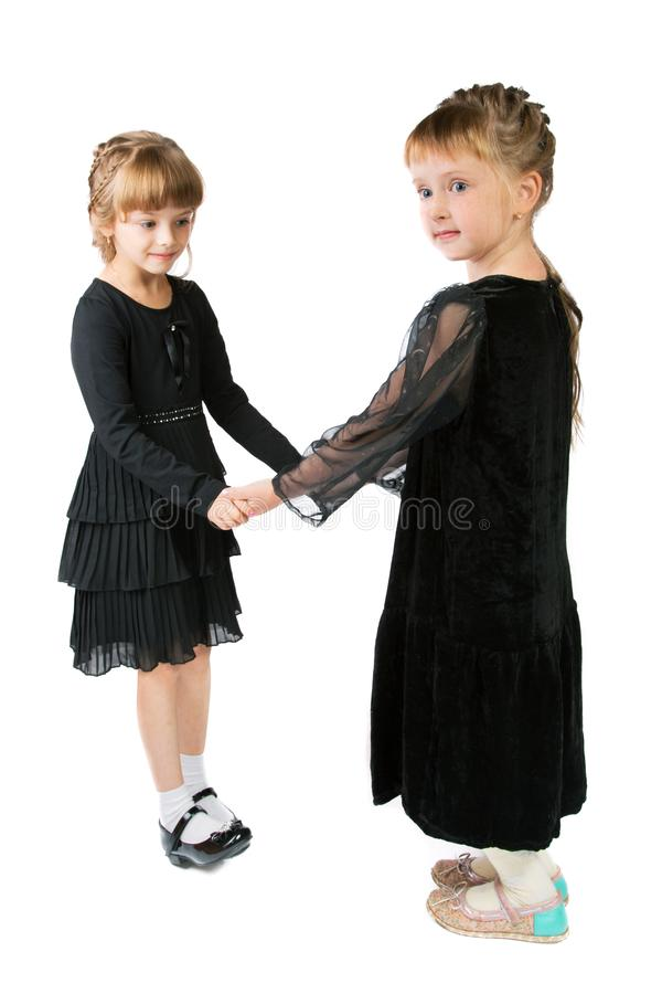 Two girls in black dresses isolated on white. Background stock photos