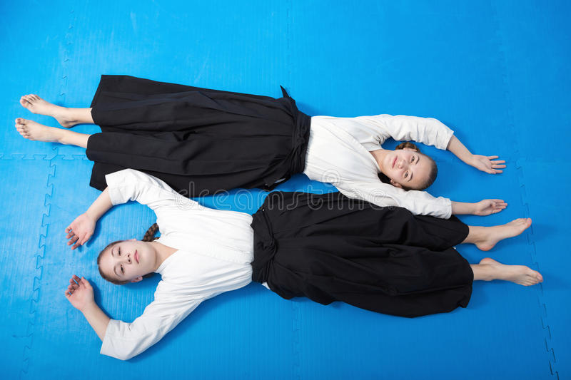 Two girls in black hakama having a rest on Aikido royalty free stock images