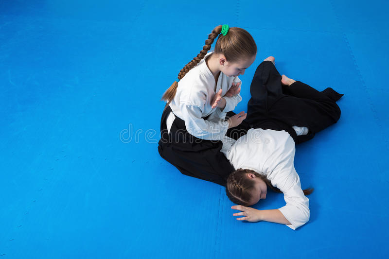 Two girls in black hakama practice Aikido royalty free stock photos