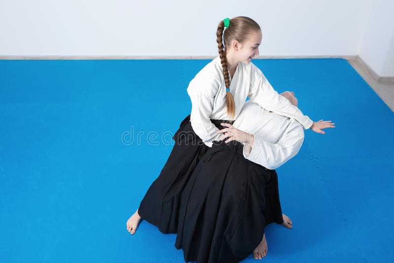 Two girls in black hakama practice Aikido royalty free stock images