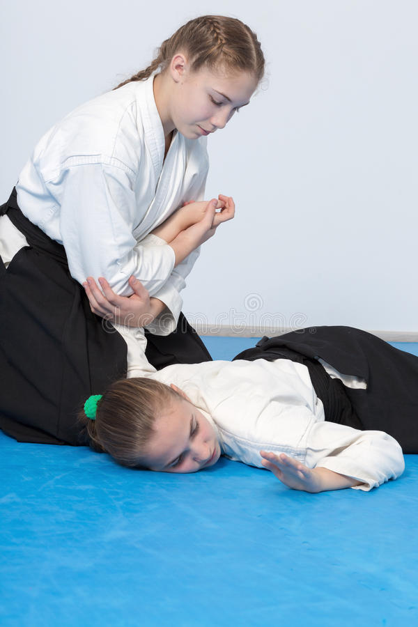Two girls in black hakama practice Aikido stock image