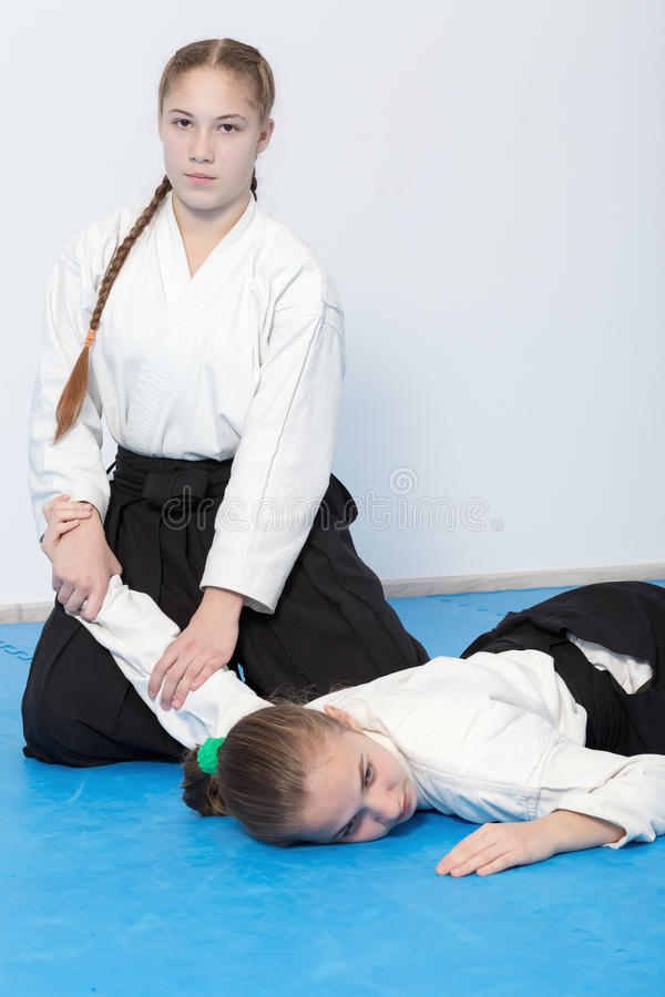 Two girls in black hakama practice Aikido. Selective focus royalty free stock images
