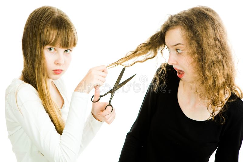 Two girls with blond hairs and scissors, one going to cut hairs to make better haircut, second with curly hairs try to avoid. Young hair stylist - white royalty free stock image