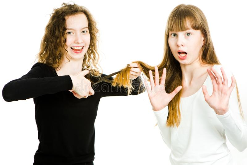 Two girls with blond hairs and scissors, one going to cut hairs stock images