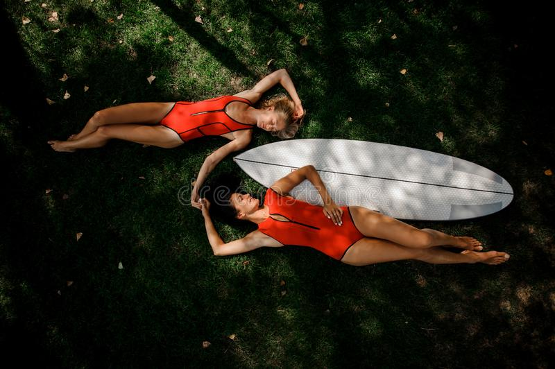 Two girls lying on the two sides of the wakeboard. Two girls, blonde and brunette, in red swimsuits lying on the two sides of the white wakeboard on the green royalty free stock image