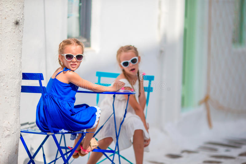 Two girls in blue dresses sitting on blue chairs and table on street of typical greek traditional village with white. Two girls in blue dresses having fun royalty free stock photo