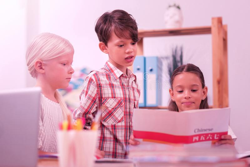 Two girls and a boy learning chinese. New language. Two girls and a boy learning chinese language sitting at the school desk with a workbook royalty free stock photos