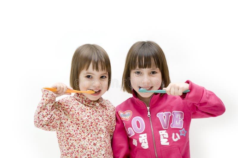 Two girls brushing his teeth royalty free stock image