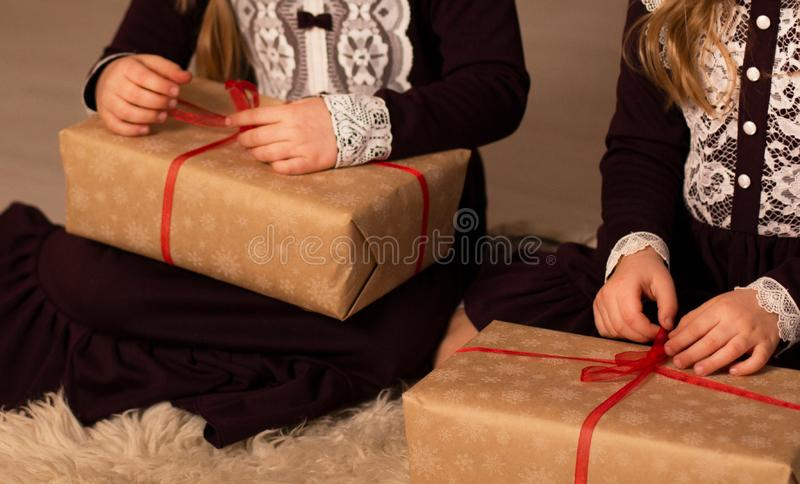 Two girls in a burgundy lace retro dress open Christmas gift stock photos