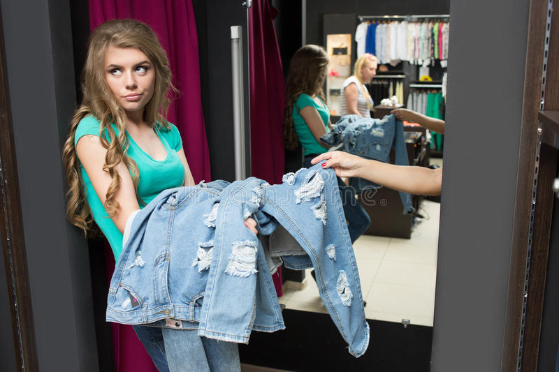 Two girls buy jeans in the store. tired girlfriend. Two beautiful girls buy jeans in the store. tired girlfriend stock photos