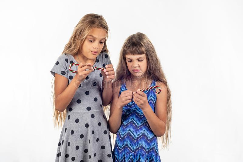 Two girls can not open the plastic packaging of caramel candies royalty free stock photos