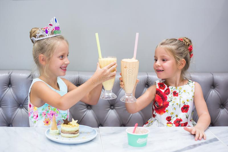 Two girls celebrate their birthday. Children`s holiday. Treats sweet, cake and juice on the table stock photos