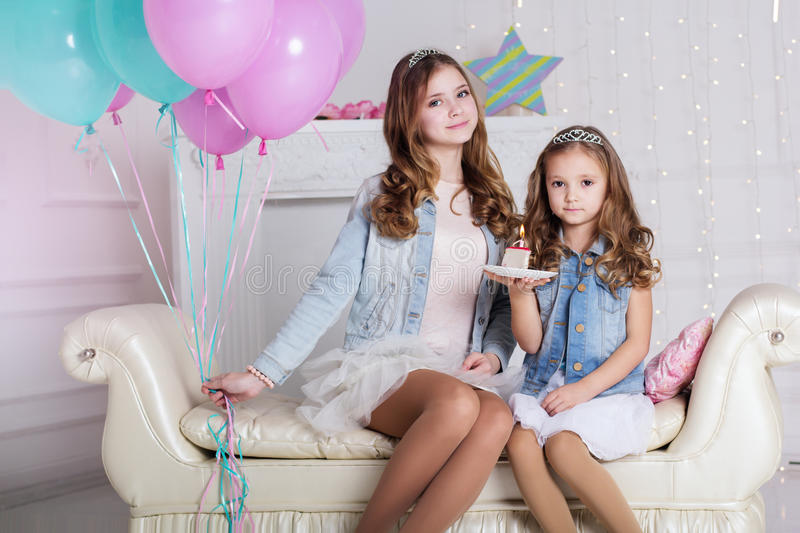 Two girls are celebrating birthday with cake. Two cute girls sisters are celebrating birthday in a studio with cake and blue and pink balloons stock images