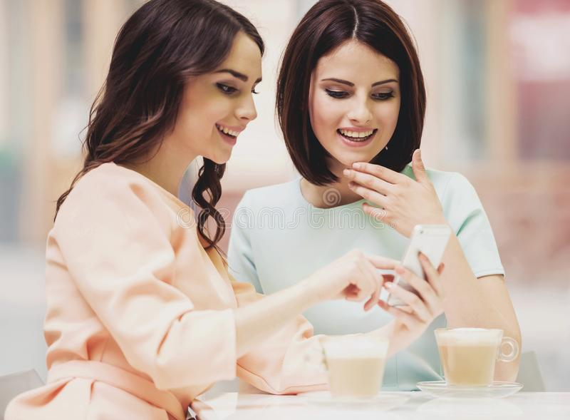 Two Girls Chatting in Cafeteria with Cups of Coffee. Two Young Attractive Smiling Brunette Women Chatting in Cafeteria with Coffe in Glass Cups. Smiling royalty free stock image