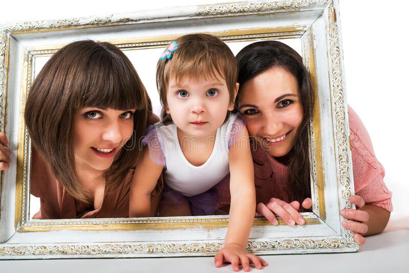Two girls and child holding wooden white frame. Photo two girls and child holding wooden white and gold frame, smiling and looking at camera stock images