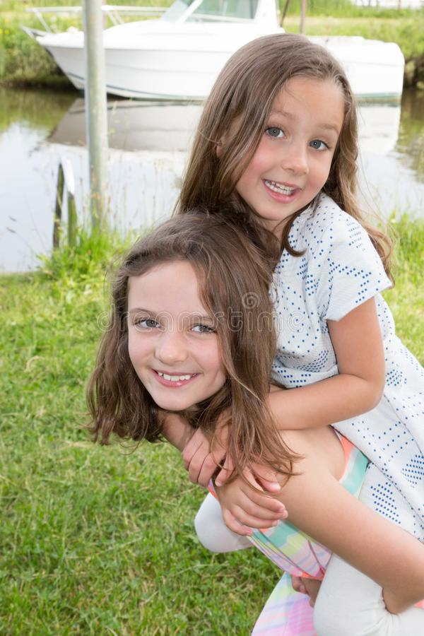 Two girls children make a piggyback concept of vacation and family love stock image