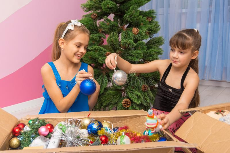 Two girls are considering balls in a box with New Year`s toys stock photography