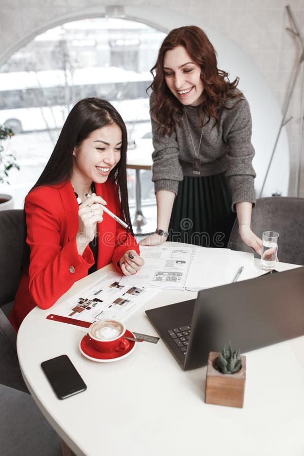 Two girls designers are working with laptop and documentation at the project in the stylish office. Project creation royalty free stock photography