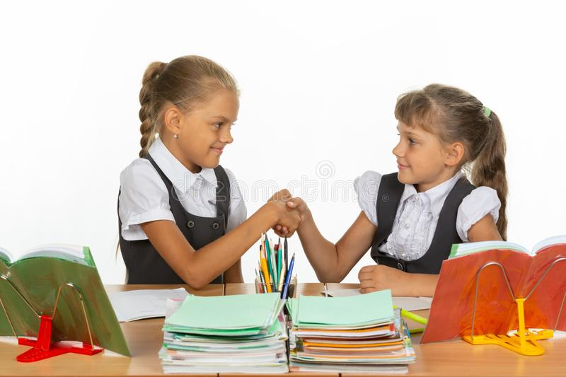 Two girls at a desk shake hands. Two  girls at a desk shake hands royalty free stock images