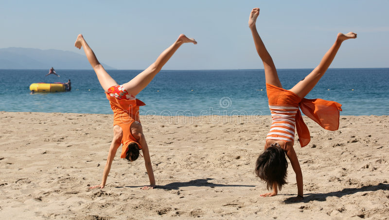 Two girls doing cartwheel stock images