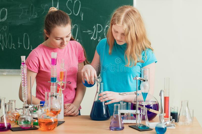 Two girls doing chemical experiments. The two girls doing chemical experiments royalty free stock images