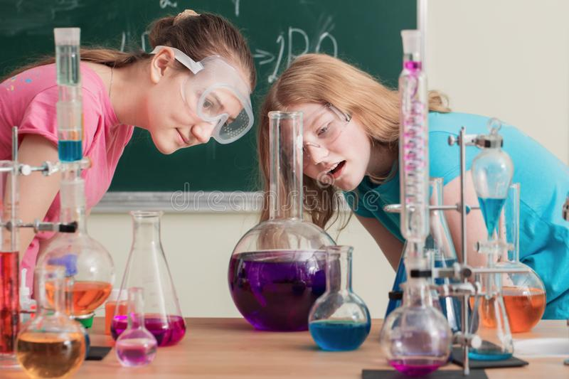 Two girls doing chemical experiments. The two girls doing chemical experiments stock photography