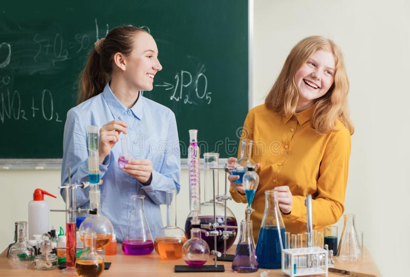Girls doing chemical experiments. Two girls doing chemical experiments royalty free stock images