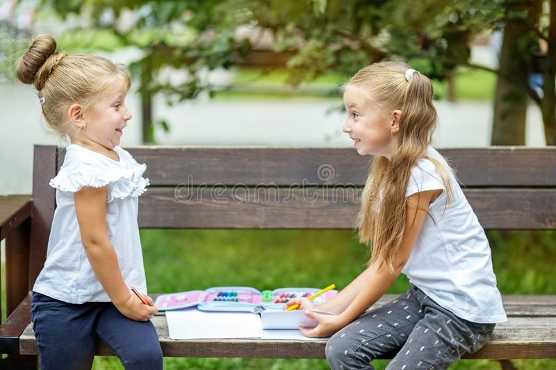 Two girls draw in the school park. Positive emotions. The concept of school, friendship, drawing, study, hobby.  stock photo