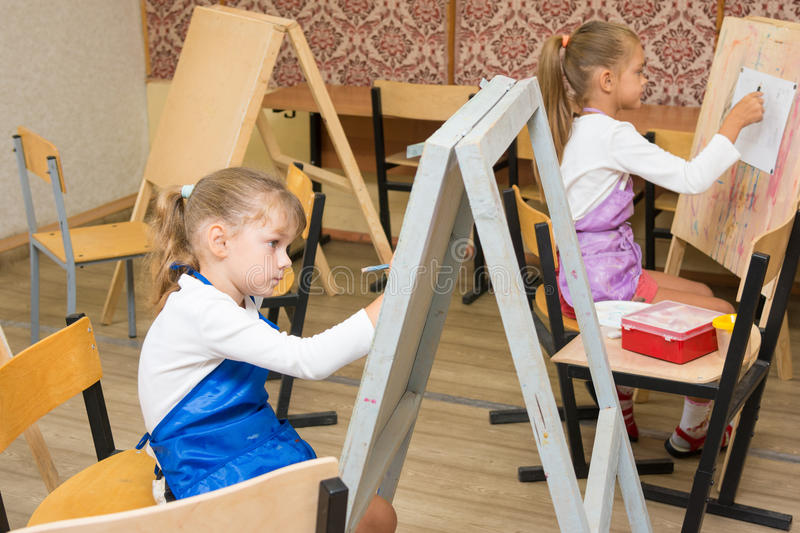 Two girls at drawing lesson paint on easels stock photos
