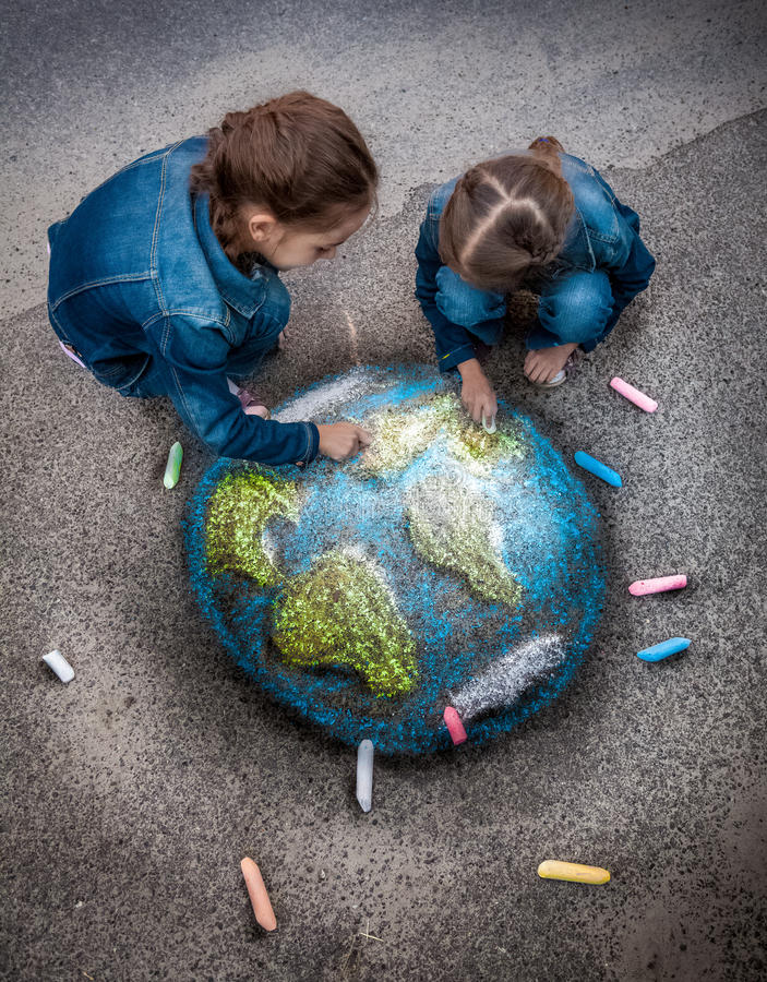 Two girls drawing realistic Earth image with chalks on ground stock photo