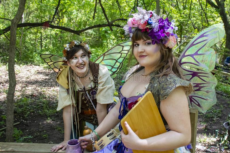 Two girls dressed as fairies in the woods - one looking mischivously at the camera and the other laughing at her at Oklahoma Renai stock image