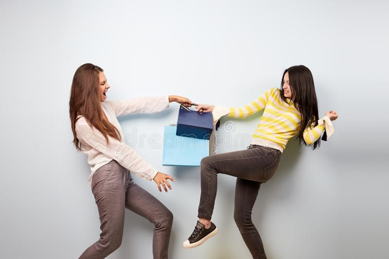 Two girls dressed in nice stylish clothes are pulling each other bags after shopping on the white background stock photos