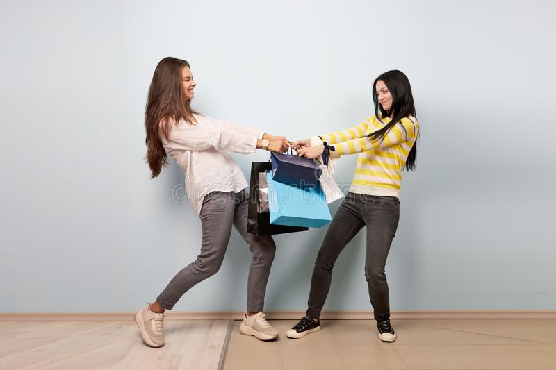 Two girls dressed in nice stylish clothes are pulling each other bags after shopping on the white background royalty free stock photo