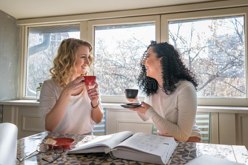 Two girls are drinking coffee and laughing in cafe royalty free stock photo