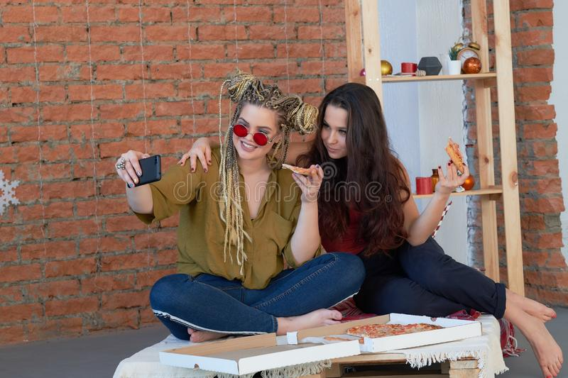 Two girls eat pizza in the room on the bed. make selfie on your smartphone. junk food. Two girls eat pizza in the room on the bed. junk food stock photography