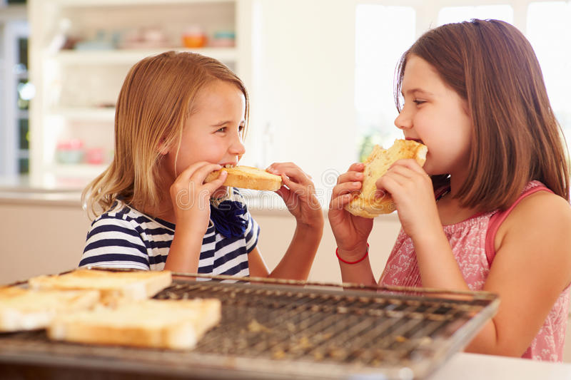 Two Girls Eating Cheese On Toast In Kitchen stock photos