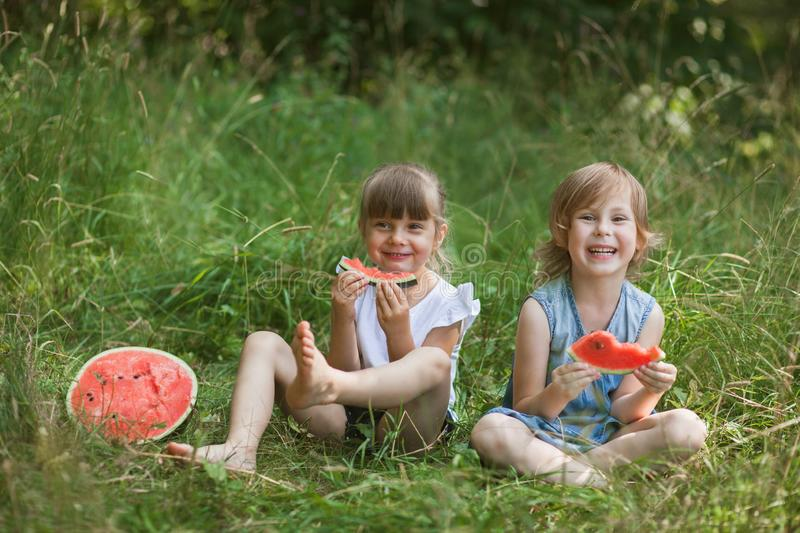 Two girls eating watermelon outdoors. Healthy snack for children royalty free stock images