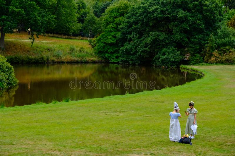 Two girls in Edwardian costumes at Lyme Hall, a historic English. Stockport, United Kingdom - July 24, 2018: Two girls in Edwardian costumes at Lyme Hall, a royalty free stock photo