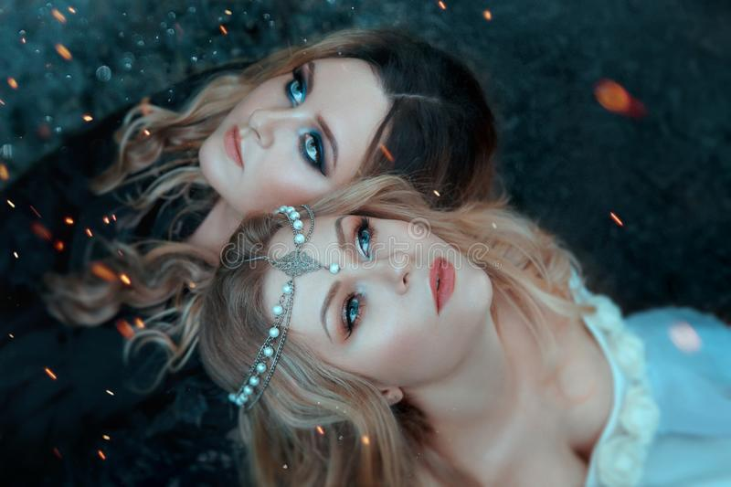 Two girls of the elements, opposites, love each other with affection. Around them, sparks, flashes of magic. Close-up. Two girls of thTwo girls of the elements royalty free stock image