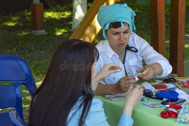 Two girls are engaged in manual creativity at the festival. Front View royalty free stock photo
