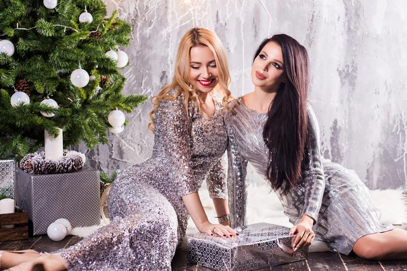 Two girls in evening dresses near the Christmas tree, the night before the new year, holiday. New Year, celebration, winter concepts stock photo