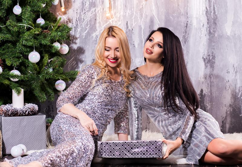 Two girls in evening dresses near the Christmas tree, the night before the new year. Holiday royalty free stock photo