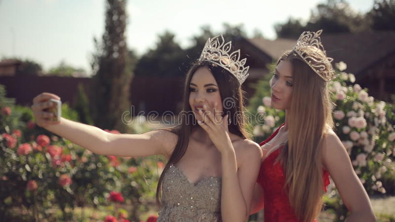 Two Girls In Evening Gowns And Crowns Make Selfie Stock Footage ...