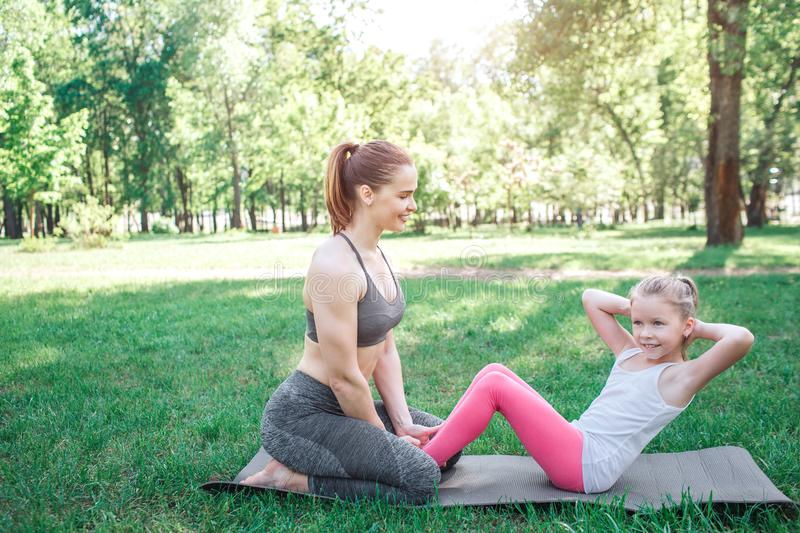 Two girls are excercising in park. Woman is sitting on her knees and holding her daughter`s feet while small girl is stock photo