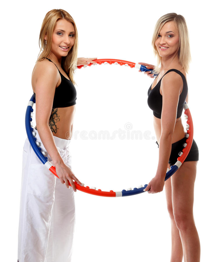 Two girls exercising with hula hoops in gym stock photos