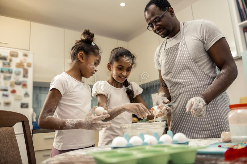 Two girls feeling excited while beating eggs for cooking pie. Girls beating eggs. Two cute funny girls feeling excited while beating eggs for cooking pie stock image