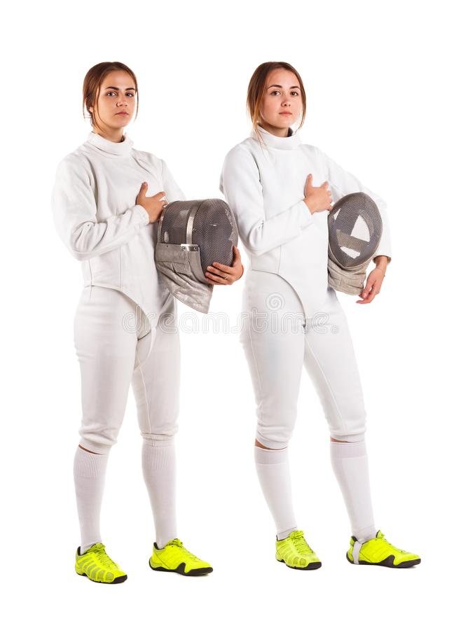 Two girls are fencers, in a uniform, one hand holding a mask and a second hand on the heart. Isolated. stock photo