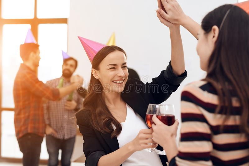 Two girls in festive caps are talking in the office. royalty free stock photos